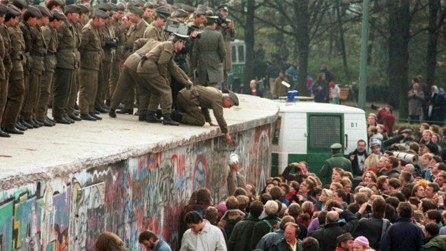 Soldati di guardia e migliaia di berlinesi che si ammassano lungo il Muro di Berlino